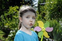 Mädchenspiele mit Windmühle Lizenzfreie Stockbilder