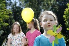 Mädchenspiele mit Windmühle Stockbilder