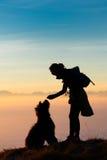 Mädchenspielen und -züge mit ihrem Schäferhund während vor, um ein BIS zu sehen stockbild