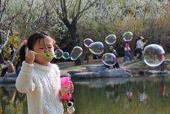 Mädchenspielluftblasen Stockfotografie