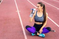 Mädchensportler crossfit und Hocken agains auf Stadionsgetränkwasser lizenzfreie stockbilder