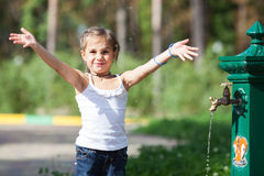 Mädchenspritzwasser am Park Stockbilder