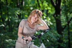 Mädchenstütze mit einem Fahrrad Stockbilder