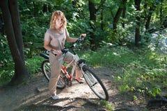 Mädchenstütze mit einem Fahrrad Lizenzfreie Stockfotos