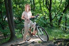 Mädchenstütze mit einem Fahrrad Stockbild