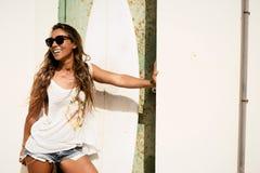 Mädchenstand mit einem Surfbrett vor Schmutztür Stockbild