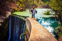 Mädchenstellung auf dem Rand bis zum watefall von sieben Frühlingen parken in Rhodos lizenzfreie stockfotos