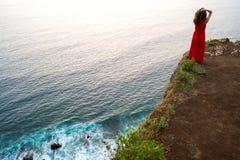 Mädchenstellung auf einem Felsen durch den Ozean, Bali-Insel lizenzfreie stockfotografie