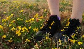 Mädchenstellung auf einem Gebiet von Blumen lizenzfreie stockfotos