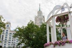 Mädchenstellung in Rundbau mit Blumen und dem Gebäude in Art Deco-Art im Abstand lizenzfreies stockfoto
