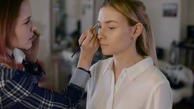 Mädchenstilist, der in einem Schönheitsstudio arbeitet Machen Sie eine schöne Blondine wieder gut Arbeiten mit Schatten stock footage