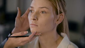 Mädchenstilist, der in einem Schönheitsstudio arbeitet Machen Sie eine schöne Blondine wieder gut Arbeiten mit Schatten stock video