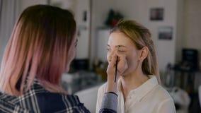 Mädchenstilist, der in einem Schönheitsstudio arbeitet Machen Sie eine schöne Blondine wieder gut Arbeiten mit Schatten stock video footage