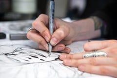Mädchentätowierungskünstler zeichnet eine Skizze Nahaufnahme der Hände Lizenzfreie Stockfotografie