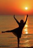 Mädchentanzen auf dem Hintergrund des Sonnenaufgangs lizenzfreie stockfotos