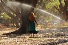 Mädchentanzen, das Wasser mit Baumhintergrund im Jungverbotpark besprüht Stockbilder