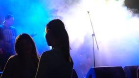 Mädchentanzen vor dem Stadium an der Leistung eines unbekannten Rockbands stock video footage