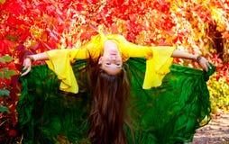 Mädchentanzen-Zigeunertanz gegen den Hintergrund des Herbstlaubs Lizenzfreie Stockfotografie
