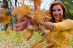Mädchenthrows-Blätter stockfotografie