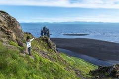 Mädchentourist, der den Hvitserkur-Basaltstapel gewaschen mit Wasser von Hindisvik-Bucht in Nordwest-Island betrachtet lizenzfreies stockbild