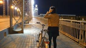 Mädchentourist in der Stadt nachts mit dem Fahrrad Die Brücken von St Petersburg stock footage
