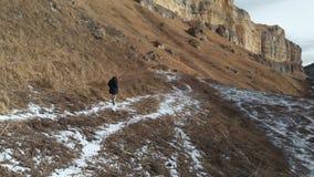 Mädchentourist in einer Abstiegjacke und in den Hutwegen entlang dem Weg im frühen Winter in einer felsigen Schlucht gelbes Gras  stock footage
