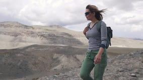Mädchentourist geht auf ein bergiges Gelände Porträt des Reisenden Frauenwanderer mit Rucksack, Berge in stock footage