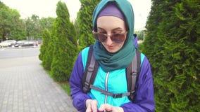 Mädchentourist im hijab in einem Rucksack benutzt das Telefon auf dem Hintergrund der Stadtlandschaft stock footage