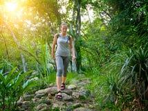 Mädchentourist mit einem Rucksack gehend entlang die Spur im jung stockfotos