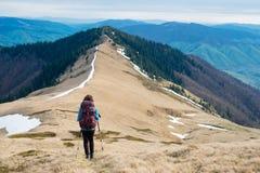 Mädchentourist mit Rucksack ist reisende Berge Lizenzfreies Stockfoto