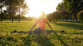 Mädchenturner sitzt auf Spalten auf dem Gras in einem Stadtpark auf der Natur und macht Wendungen in der Rückseite und im Ausdehn stockfotos