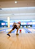 Mädchenuhren versessen an den Bowlingspielkugelrollen Lizenzfreie Stockfotografie
