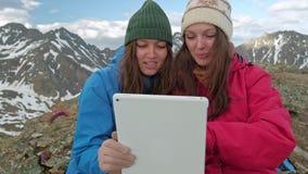 Mädchenwanderer mit einer Tablette, die auf einem Felsen auf einem Hintergrund von Bergen und von Seen, Norwegen sitzt stock footage