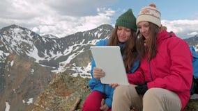 Mädchenwanderer mit einer Tablette, die auf einem Felsen auf einem Hintergrund von Bergen und von Seen, Norwegen sitzt stock video