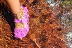 Mädchenwasserfüße zacken Schuh im Flussstrom aus Stockfoto