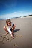 Mädchenzeichnung im Strandsand Lizenzfreie Stockfotos