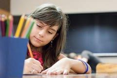 Mädchenzeichnung mit farbigen Bleistiften Lizenzfreie Stockfotografie