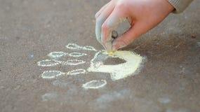 Mädchenzeichnung mit farbiger Kreide auf der Pflasterung Stockbild