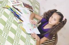 Mädchenzeichnung mit Zeichenstiften Stockbilder