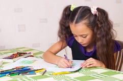 Mädchenzeichnung mit Zeichenstiften Lizenzfreies Stockfoto