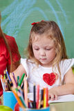 Mädchenzeichnung mit Zeichenstiften Stockfoto