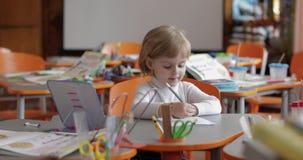 Mädchenzeichnung am Tisch im Klassenzimmer Ausbildung Kind, das an einem Schreibtisch sitzt stock video footage