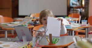 Mädchenzeichnung am Tisch im Klassenzimmer Ausbildung Kind, das an einem Schreibtisch sitzt stock video
