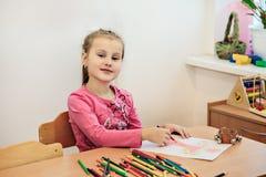 Mädchenzeichnungsfarbe zeichnet im Kindergartenklassenzimmer-, -vorschule- und -kinderbildungskonzept an stockfotografie