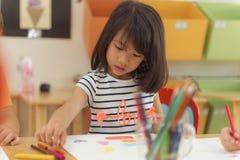 Mädchenzeichnungsfarbe zeichnet im Kindergartenklassenzimmer-, -vorschule- und -kinderbildungskonzept an Stockfoto