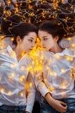 Mädchenzwillinge mit Lichtern Neues Jahr ` s Eve Weihnachten Gemütlicher Feiertag am Tannenbaum mit Lichtern und Golddekor stockfotos