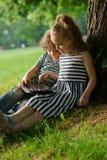 Mädel mit Jungen sitzen unter einem anschmiegenden Baum und Spiel auf der Tablette Stockbild
