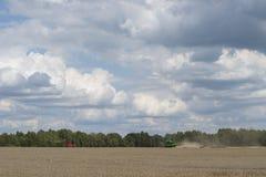 Mähdrescher auf einem Feld mit bewölkten Himmeln Stockbilder