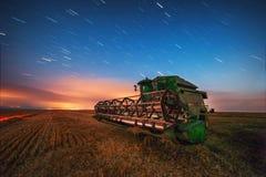 Mähdreschermaschine, die auf einem Weizengebiet, -sonnenuntergang und -s arbeitet Lizenzfreies Stockfoto