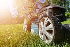Mähende Rasen, Rasenmäher auf grünem Gras, Mähergrasausrüstung, mähendes Gärtnersorgfalt-Arbeitswerkzeug, Abschluss herauf Ansich stockfoto